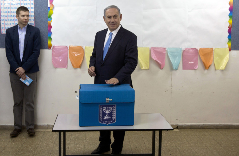 Israel's Prime Minister Benjamin Netanyahu casts his ballot for the parliamentary election as his son Yair stands behind him at a polling station in Jerusalem March 17, 2015. (photo credit: SEBASTIAN SCHEINER/POOL VIA REUTERS)