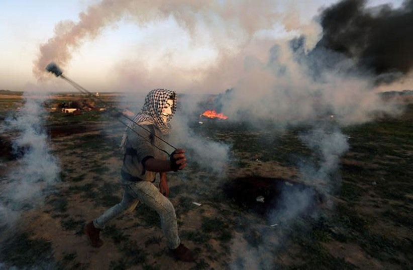 A Palestinian demonstrator uses a sling to hurl back a tear gas canister fired by Israeli troops during a protest at the Israel-Gaza border fence (photo credit: REUTERS/IBRAHEEM ABU MUSTAFA)
