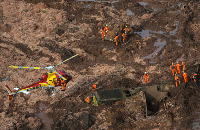 Rescue crew work in a tailings dam owned by Brazilian miner Vale SA that burst, in Brumadinho (photo credit: WASHINGTON ALVES / REUTERS)