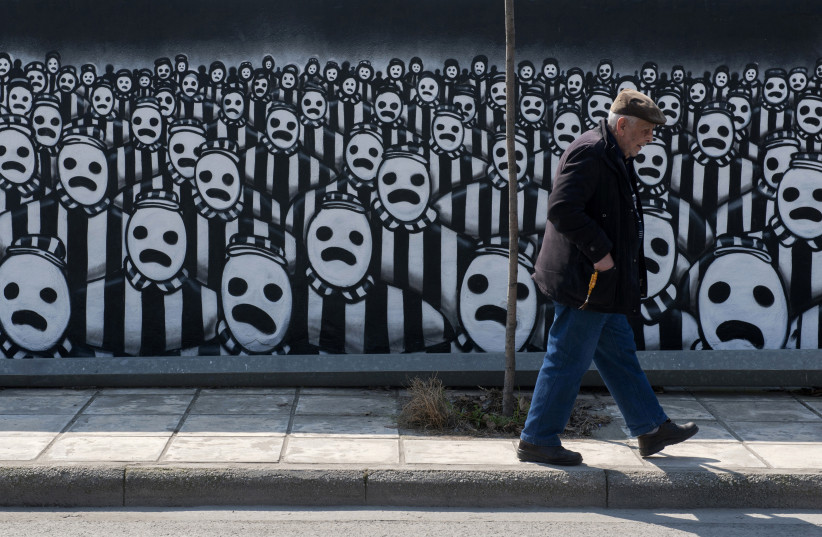 A man walks past a graffiti dedicated to the Holocaust in the northern port city of Thessaloniki (photo credit: ALEXANDROS AVRAMIDIS/REUTERS)
