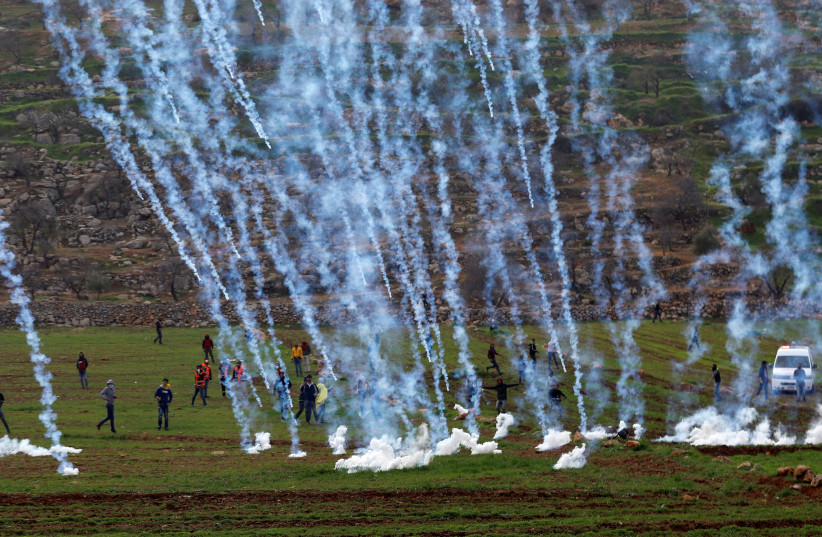 Tear gas canisters are fired by Israeli forces towards Palestinians during clashes in al-Mughayer village near Ramallah, January 27, 2019.  (photo credit: MOHAMAD TOROKMAN/REUTERS)