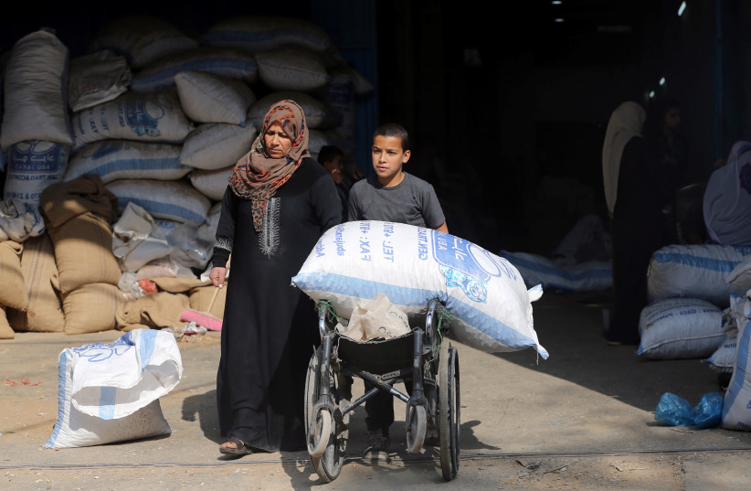 A Palestinian boy uses a wheelchair to transport a bag of peanuts as he helps his mother who makes a living by peeling peanuts for a factory, in Rafah in the southern Gaza Strip January 22, 2019. (photo credit: IBRAHEEM ABU MUSTAFA / REUTERS)
