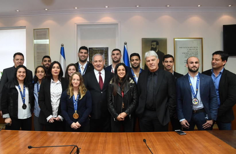 Prime Minister Benjamin Netanyahu and Minister of Culture and Sport Miri Regev meet in the prime minister's office with medal winners of the Grand Prix judo tournament. (photo credit: CHAIM TZACH/GPO)