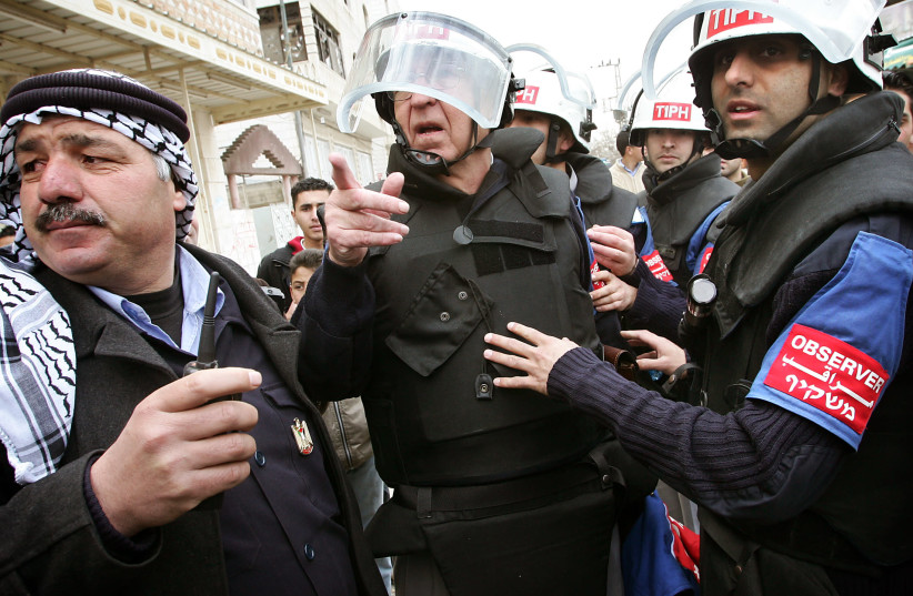 Arnstein Overkil, the Norwegian head of the TIPH observer team (C) coordinates with his staff and a Palestinian police officers outside TIPH headquarters in the West Bank city of Hebron February 8, 2006 (photo credit: DAMIR SAGOLJ/ REUTERS)