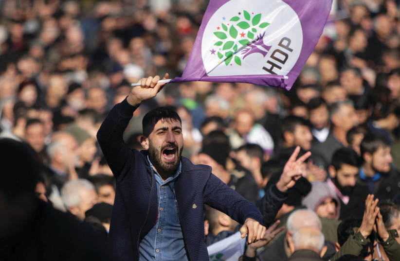 A SUPPORTER of the pro-Kurdish Peoples' Democratic Party protests earlier this month in Diyarbakir, Turkey.  (photo credit: SERTAC KAYAR / REUTERS)