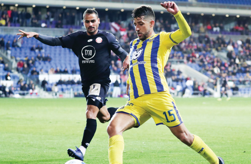 MACCABI TEL AVIV midfielder Dor Micha (15) set up both of his side's goals in the runaway-leader yellow-and-blue's 2-0 victory over Hapoel Hadera in Israel Premier League action on Monday night (photo credit: DANNY MARON)