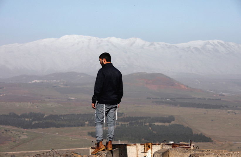 A MAN stands at Mount Bental, an observation post on the Golan Heights that overlooks the Syrian side of the Quneitra crossing, on January 21. (photo credit: REUTERS)