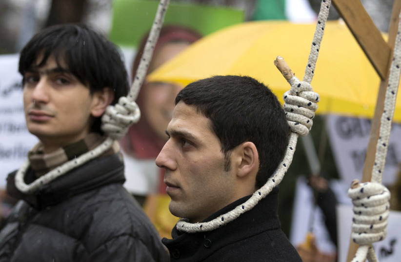 People stage a mock hanging as they protest outside German Council on Foreign Relations in Berlin February 4, 2013, where Iran's Foreign Minister Ali Akbar Salehi's was due to deliver a speech. (photo credit: THOMAS PETER/REUTERS)