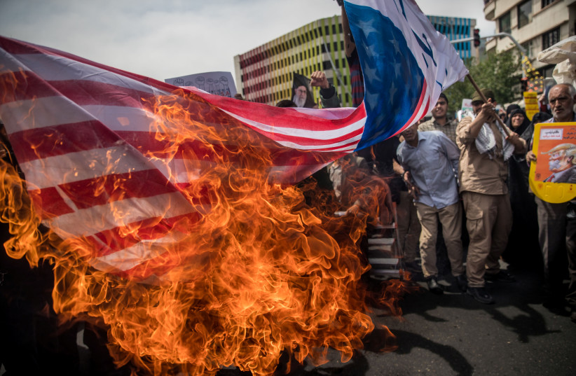 Iranians burn a U.S. flag during a protest against President Donald Trump's decision to walk out of a 2015 nuclear deal, in Tehran, Iran, May 11, 2018.  (photo credit: REUTERS)