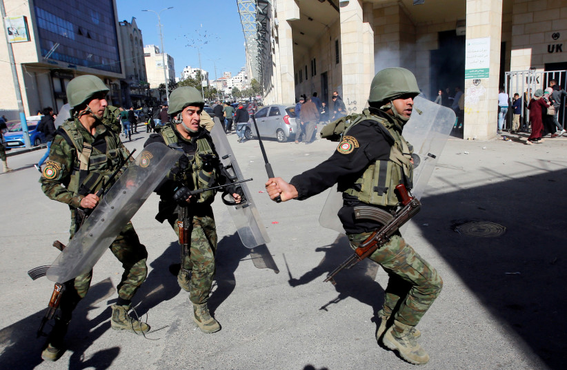 Members of Palestinian security forces disperse a Hamas demonstration in Hebron in the West Bank. December 14, 2018.  (photo credit: MUSSA QAWASMA / REUTERS)