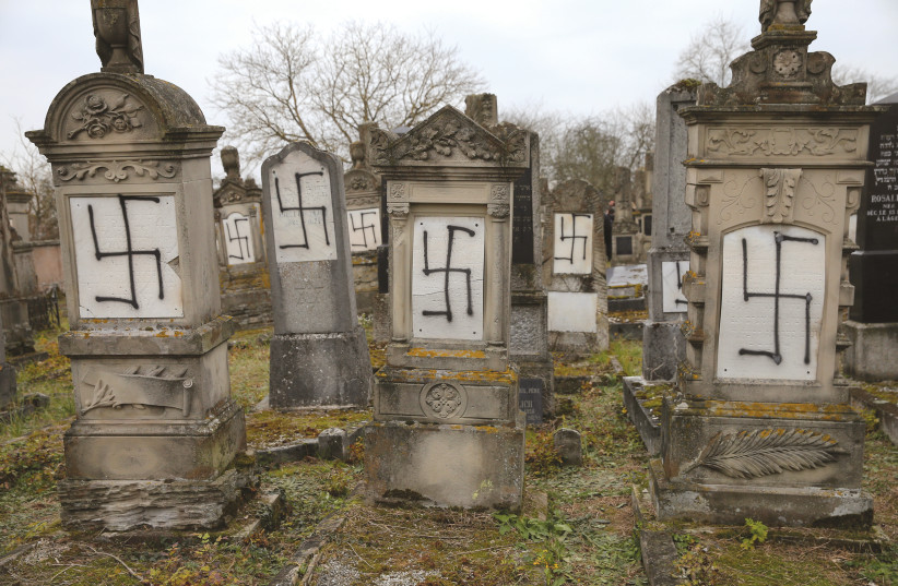 GRAVES DESECRATED with swastikas are seen in the Jewish cemetery of Herrlisheim.  (photo credit: REUTERS)