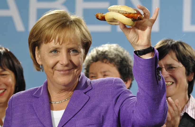 German Chancellor Angela Merkel holds up a traditional Thuringia sausage in Erfurt following an election campaign tour in the historic 'Rheingold Express' train through Germany September 15, 2009. (photo credit: WOLFGANG RATTAY / REUTERS)