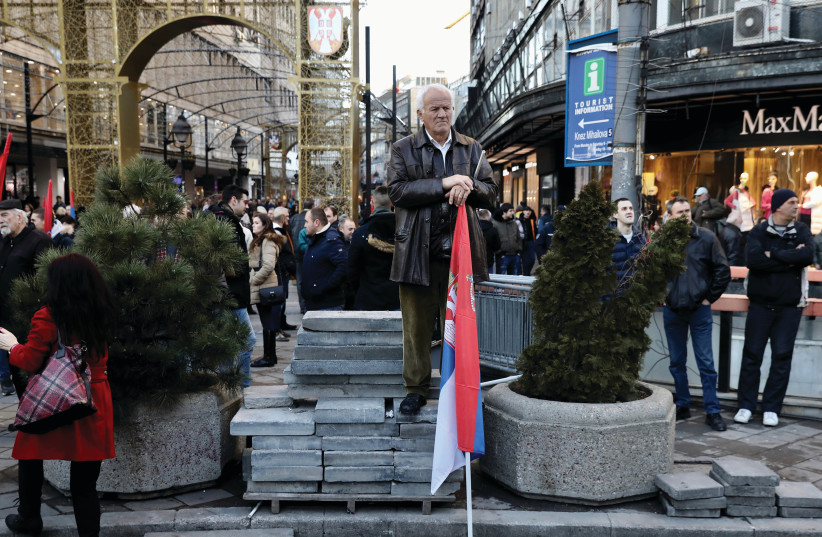 A MAN holds a Serbian flag on a street corner in Belgrade (photo credit: REUTERS)