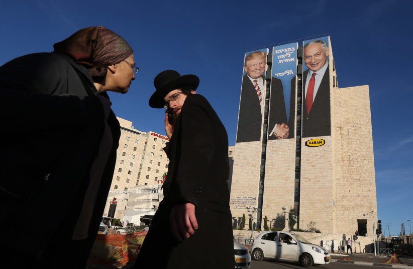 Residents of Jerusalem watch a billboard ad in which Prime Minister Benjamin Netanyahu is seen shaking hands with U.S. President Donald Trump, caption says: Netanyahu is in a whole other league   (photo credit: MARC ISRAEL SELLEM)