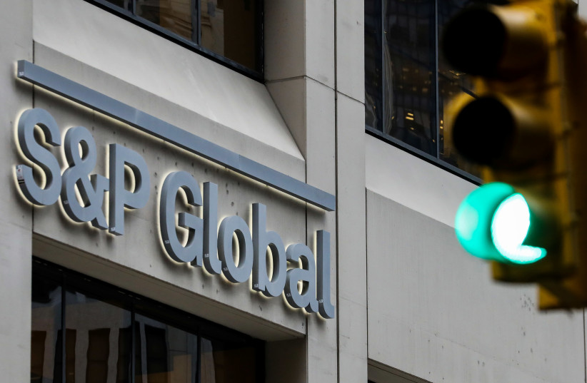 The S&P Global logo is displayed on its offices in the financial district in New York City (photo credit: BRENDAN MCDERMID/REUTERS)