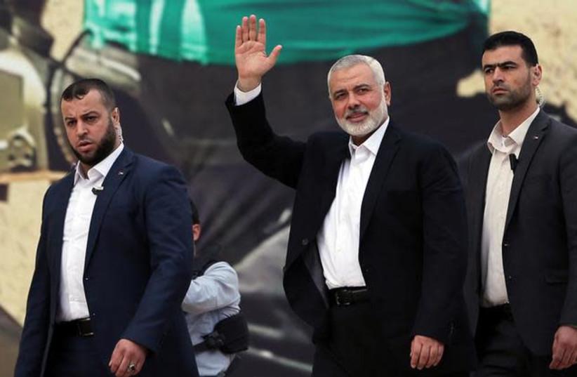 Hamas Chief Ismail Haniyeh gestures during a rally marking the 31st anniversary of Hamas' founding (photo credit: REUTERS/IBRAHEEM ABU MUSTAFA)