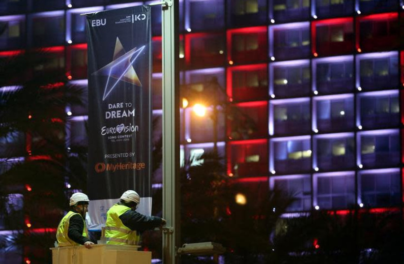 Labourers stand on a crane as they hang 2019 Eurovision Song Contest banners in Tel Aviv, Israel January 24, 2019 (photo credit: REUTERS/CORINNA KERN)