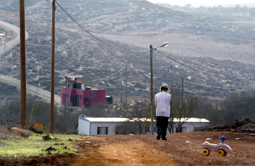 A Jewish settler walks at the Jewish settlement outpost of Adei Ad B in the West Bank (photo credit: REUTERS/NIR ELIAS)