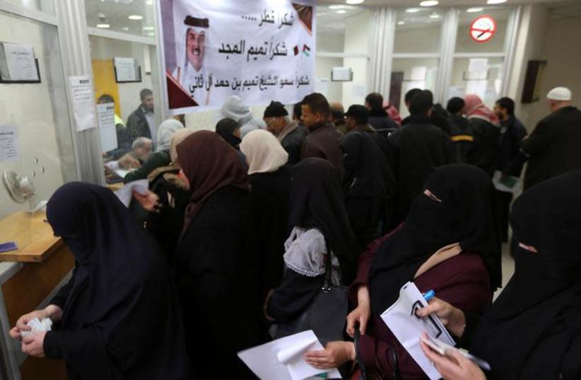 Palestinian Hamas-hired civil servants wait to receive their salaries paid by Qatar (photo credit: REUTERS/IBRAHEEM ABU MUSTAFA)