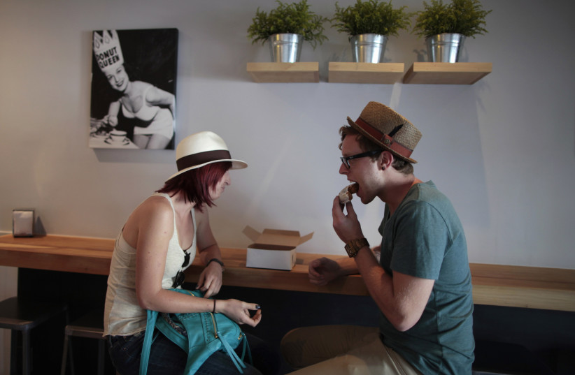 Ali Leopold, 24, (L) and Andrew Herrold, 25, eat faux donuts at Fonuts bakery, which offers unfried, gluten-free and vegan donuts, in Los Angeles, California September 19, 2011. An estimated 18 million people in the United States are sensitive to gluten, a hard-to-digest protein found in wheat, rye  (photo credit: LUCY NICHOLSON / REUTERS)