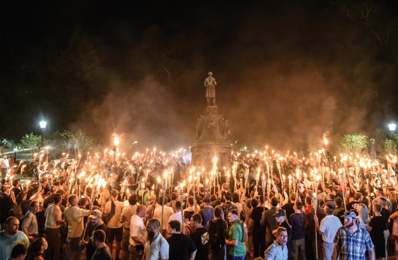 American white nationalists march at the University of Virginia ahead of the Unite the Right Rally in Charlottesville, Virginia, on August 11, 2017. In Charlottesville, antisemitic marchers shouted, 'Jews won't replace us' (photo credit: STEPHANIE KEITH/REUTERS)