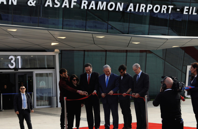The three Ramon children, Tal, Noa and Yiftach, join Prime Minister Benjamin Netanyahu and Transportation Minister Israel Katz and Israel Airports Authority CEO Yaakov Ganot in cutting a red ribbon at the inauguration of the Ramon Airport on January 21, 2019 (photo credit: RONEN ZVULUN)