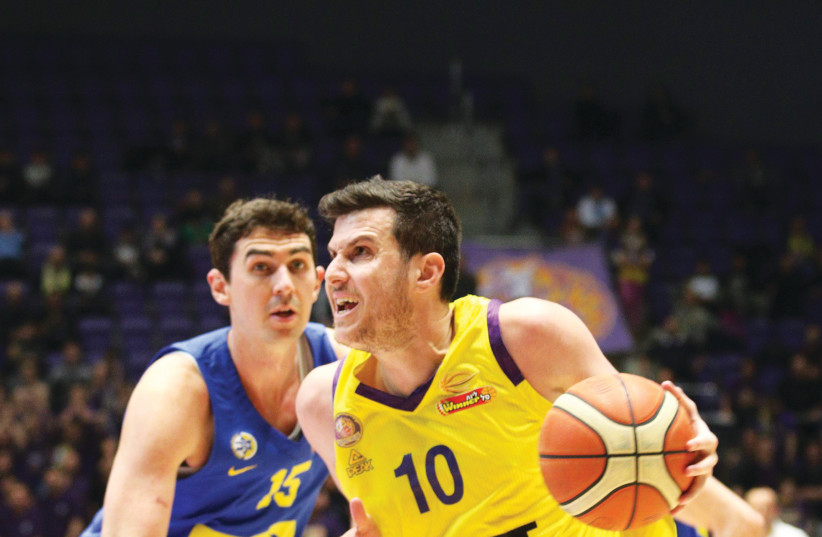 HAPOEL HOLON'S Guy Pnini (10) drives to the hoops past Maccabi Tel Aviv's Jake Cohen during Holon's 100-95 victory over the yellow-and-blue on Sunday night in BSL action (photo credit: ADI AVISHAI)