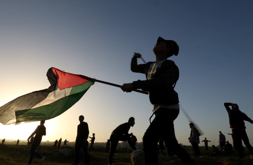 A demonstrator holding a Palestinian flag uses a sling to hurl stones at Israeli troops during a protest at the Israel-Gaza border fence, in the central Gaza Strip January 25, 2019 (photo credit: IBRAHEEM ABU MUSTAFA / REUTERS)
