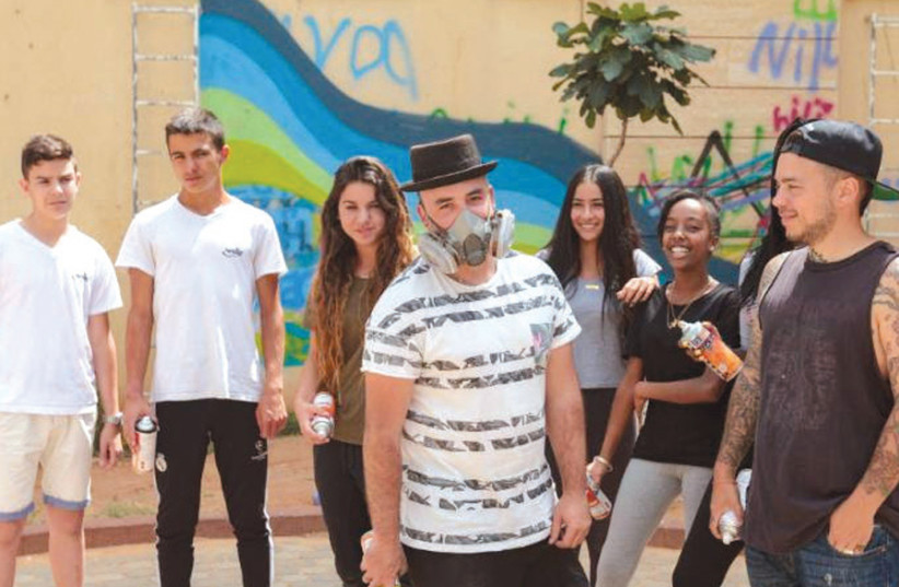 Artists 4 Israel's Pariz One and Dershowitz help children in Netanya transform the outside of their school into a work of art (photo credit: ARTISTS 4 ISRAEL)