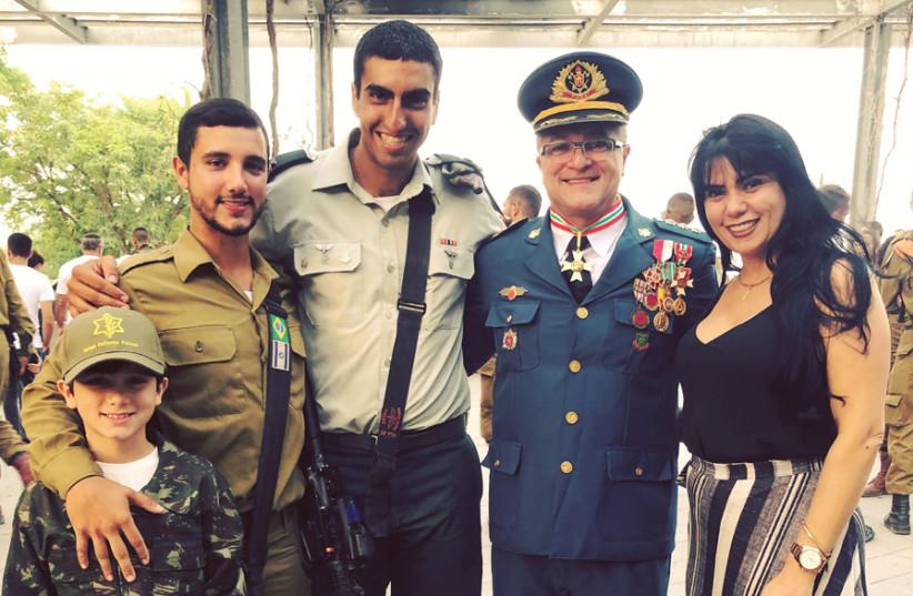 FERNANDO LARRAT MIRANDA (second left) with his young brother David, Kfir company commander Rubi Gorgi, his father Colonel Fernando, and his mother Michele at his combat ceremony. (photo credit: Courtesy)