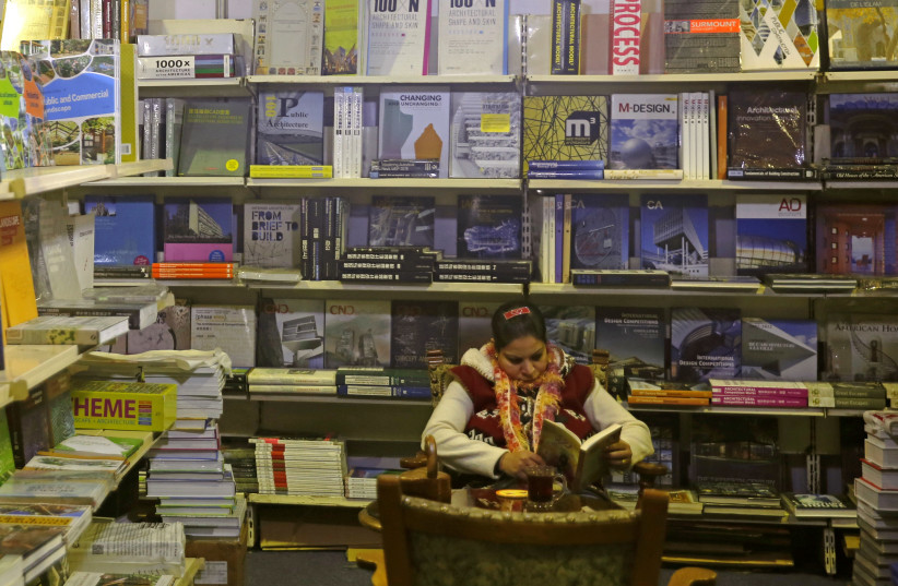 A woman reads a book inside the 49th Cairo International Book Fair in Cairo, Egypt February 1, 2018 (photo credit: AMR ABDALLAH DALSH / REUTERS)