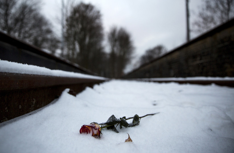 A flower lies in the train tracks at Gleis 17 memorial in Berlin, where thousands of Holocaust victims were deported to concentration camps (photo credit: THOMAS PETER/REUTERS)