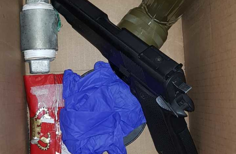 Weapons, ammunition and an improvised explosive was found in a home during a raid on Thursday (photo credit: ISRAEL POLICE)