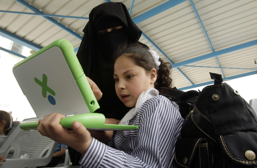 A teacher shows a Palestinian schoolgirl how to use a new laptop at a United Nations school in Gaza, April 29, 2010. (photo credit: IBRAHEEM ABU MUSTAFA / REUTERS)