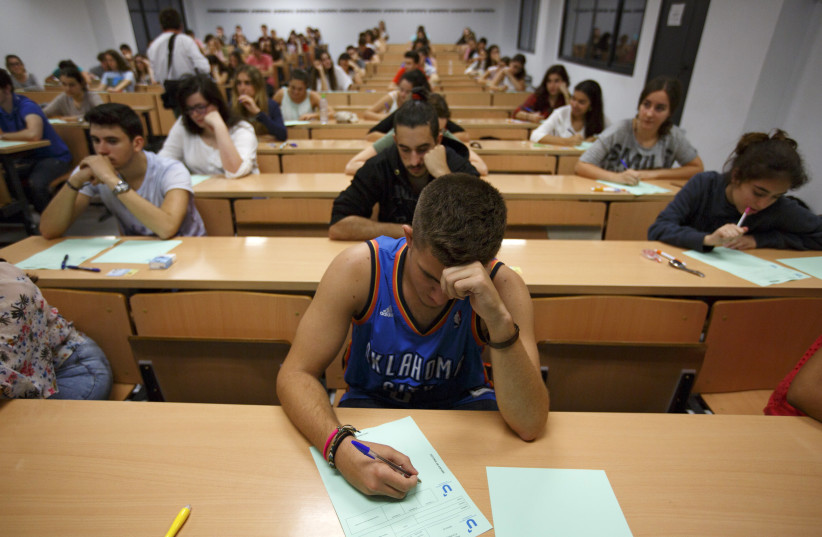 Students take a university entrance examination at a lecture hall in the Andalusian capital of Seville, southern Spain, June 16, 2015. Students in Spain must pass the exam after completing secondary school in order to gain access to university. REUTERS/Marcelo del Pozo (photo credit: MARCELO DEL POZO/REUTERS)