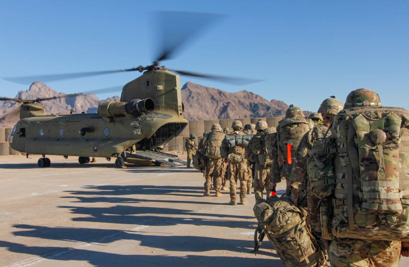Soldiers attached to the 101st Resolute Support Sustainment Brigade, Iowa National Guard and 10th Mountain, 2-14 Infantry Battalion, load onto a Chinook helicopter to head out on a mission in Afghanistan, January 15, 2019. 1st Lt. Verniccia Ford/U.S.  (photo credit: VERNICCIA FORD/U.S. ARMY/HANDOUT VIA REUTERS)