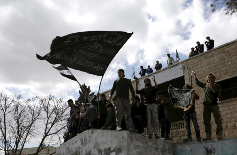 Protesters carry Al-Qaeda flags during an anti-government protest after Friday prayers in the town of Marat Numan in Idlib province, Syria (photo credit: KHALIL ASHAWI / REUTERS)