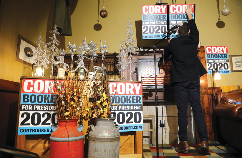 A CORY Booker supporter puts up a placard.  (photo credit: REUTERS)