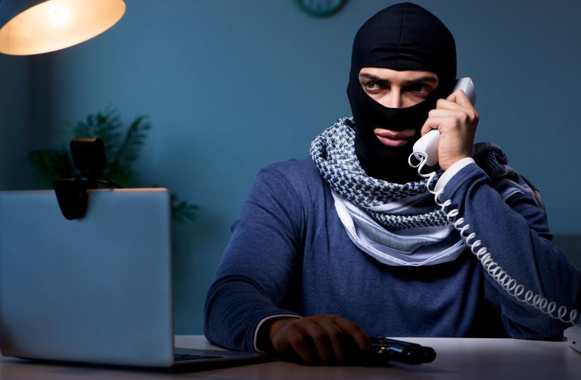 Terrorist burglar with gun working at computer (photo credit: INGIMAGE)