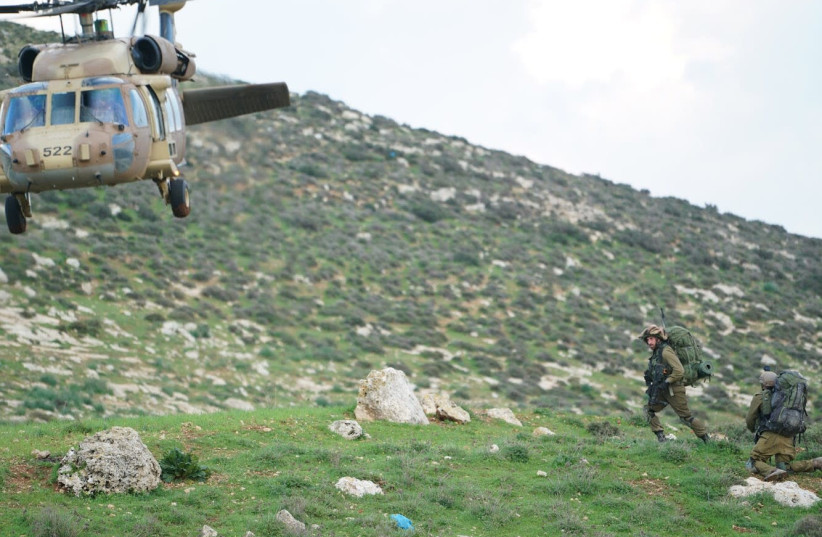 An IDF helicopter and soldiers during a training exercise for the 401th Brigade (photo credit: IDF SPOKESMAN'S UNIT)