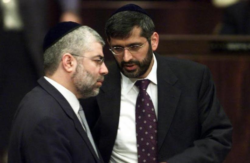 Shlomo Benizri (L) speaks with Eli Yishai (R) in the Knesset in 2001 (photo credit: NATALIE BEHRING / REUTERS)