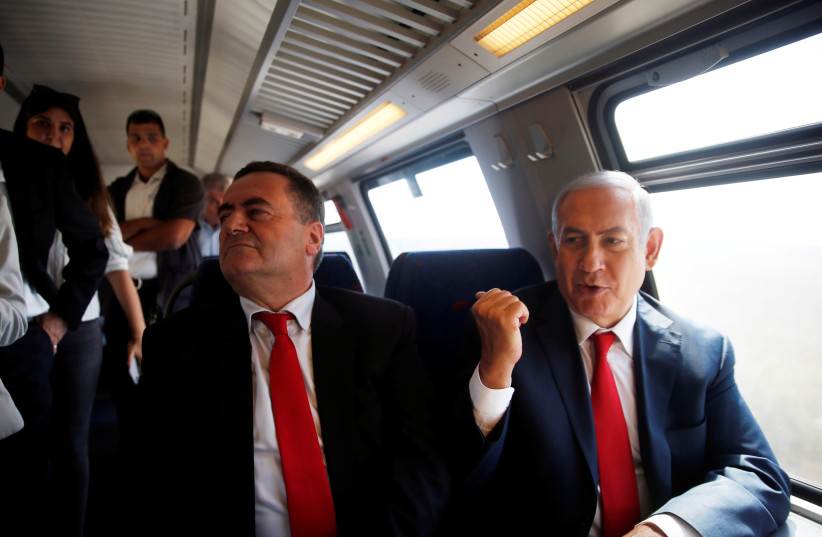 Prime Minister Benjamin Netanyahu (R) sits next to Transportation and Intelligence Minister Israel Katz (L) during a test-run of the new high-speed train between Jerusalem and Tel Aviv, near Lod, Israel September 20, 2018 (photo credit: RONEN ZVULUN/REUTERS)