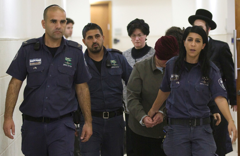 Malka Leifer, a former Australian school principal who is wanted in Australia on suspicion of sexually abusing students, walks in the corridor of the Jerusalem District Court accompanied by Israeli Prison Service guards, in Jerusalem February 14, 2018 (photo credit: REUTERS)