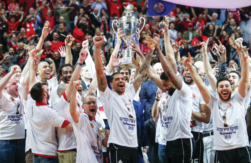 HAPOEL JERUSALEM celebrates on the court with the trophy following its victory over Maccabi Rishon Lezion in last week's State Cup final in the capital (photo credit: DANNY MARON)