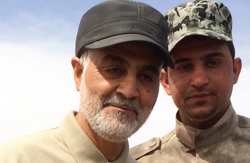 Iranian Revolutionary Guard Commander Qassem Soleimani (left) stands on the frontlines during an offensive operation against Islamic State in the town of Tal Ksaiba, in Iraq, in 2015 (photo credit: STRINGER/ REUTERS)