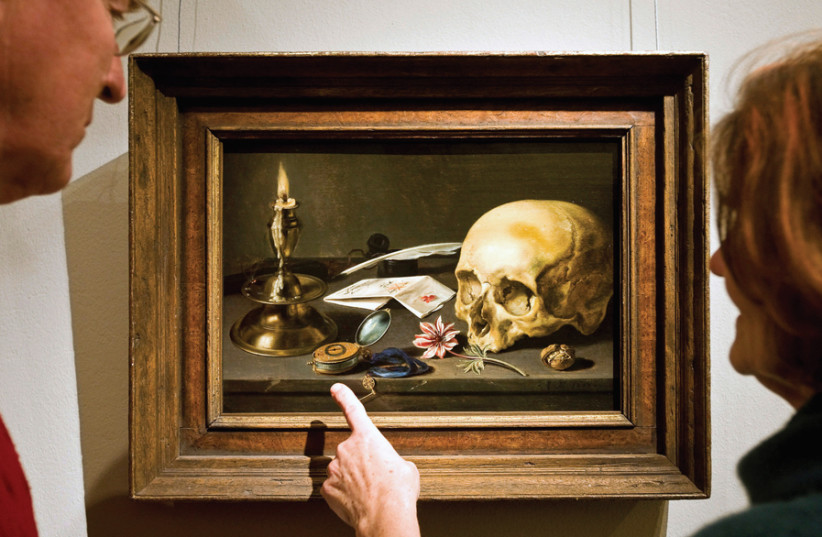 Visitors look at painter Pieter Claesz's 'Vanitas' still life in the Frans Hals Museum in Haarlem, the Netherlands; snuffed-out candles, skulls and hourglasses were how the Old Masters portrayed the vanity of greed (photo credit: ROBIN VAN LONKHUIJSEN / UNITED PHOTOS / REUTERS)