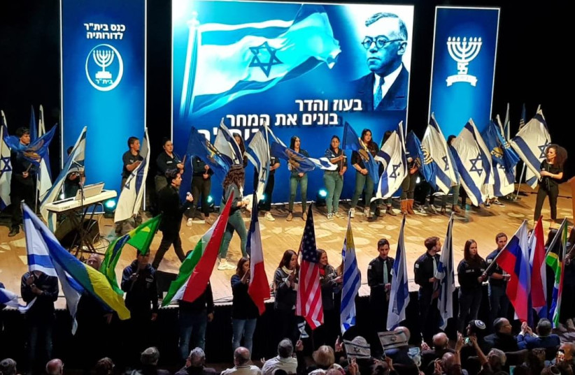 Betar youth wave Israeli flags and those of their respective countries as veteran members look on during the 95th anniversary of the youth movement in Jerusalem, February 17, 2019 (photo credit: Courtesy)