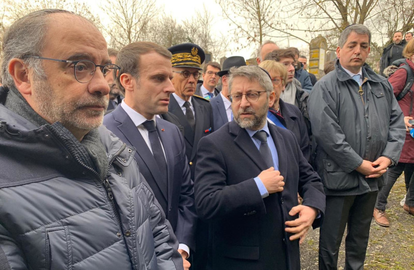 President of France Emmanuel Macron (center) visits the desecrated Quatzenheim cemetery in eastern France on Tuesday (photo credit: YONAH JEREMY BOB)