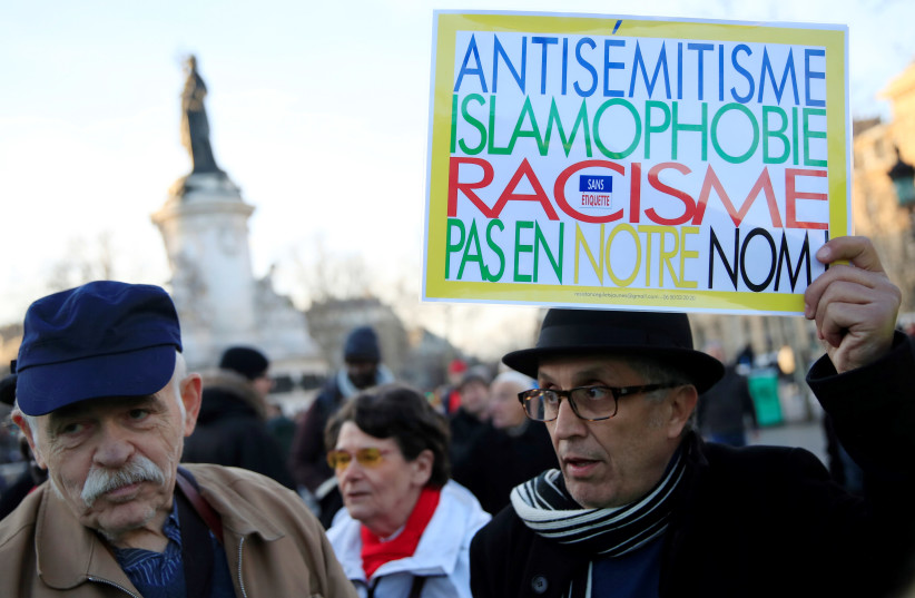 """People attend a national gathering to protest antisemitism and the rise of antisemitic attacks in the Place de la Republique in Paris, France, February 19, 2019. The writing on the sign reads: """"Antisemitism, islamophobia, racism - not in our name"""" (photo credit: REUTERS/GONZALO FUENTES)"""