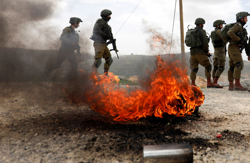 Israeli soldiers stand during clashes with Palestinians in the West Bank (photo credit: MOHAMAD TOROKMAN/REUTERS)